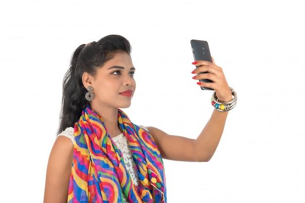 Młoda indiańska dziewczyna używa telefon komórkowego lub smartphone odizolowywających na białej ścianie