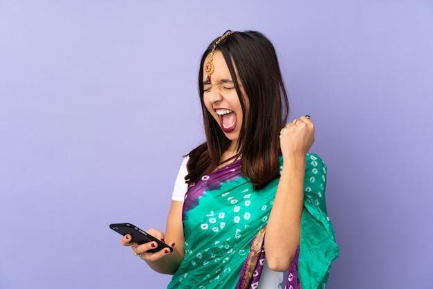 Młoda indiańska kobieta na purpurach izoluje z telefonem w zwycięstwo pozyci