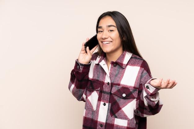 Młoda indiańska kobieta odizolowywająca na beżowej ścianie utrzymuje rozmowę z telefonem komórkowym z kimś