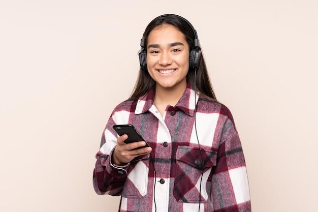Młoda indiańska kobieta odizolowywająca na beżowej ściany słuchającej muzyce z telefonem komórkowym i przyglądającym przodem