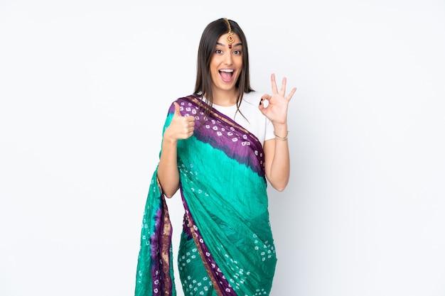 Młoda indiańska kobieta odizolowywająca na biel ścianie pokazuje ok znaka i kciuka up gestykuluje