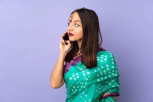 Młoda indiańska kobieta odizolowywająca na purpurowym tle utrzymuje rozmowę z telefonem komórkowym z kimś