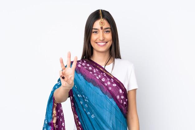 Młoda indiańska kobieta szczęśliwa na białej ścianie i liczy trzy z palcami