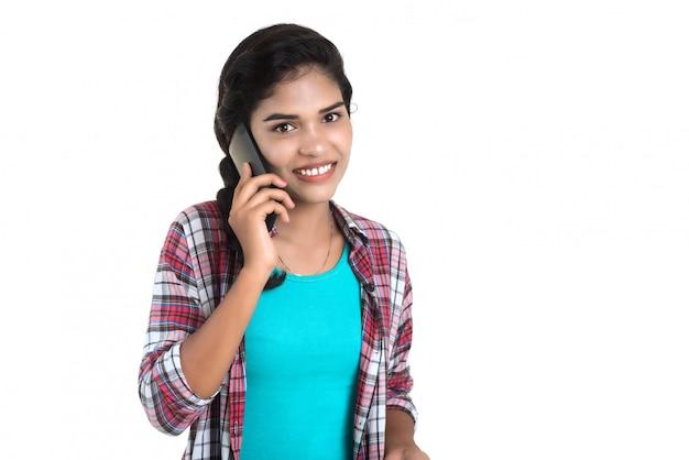 Młoda indiańska kobieta używa telefon komórkowego lub smartphone odizolowywających na białej ścianie