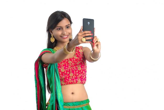 Młoda indiańska kobieta używa telefon komórkowego lub smartphone, opowiada selfie lub opowiada na wideo gadce odizolowywającej na białej ścianie