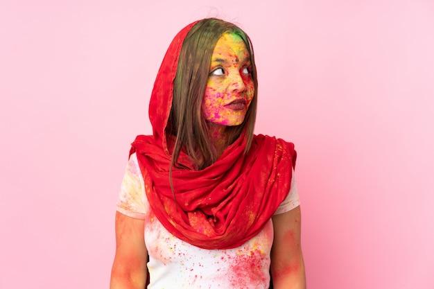 Młoda indiańska kobieta z kolorowymi holi proszkami na jej twarzy na menchii ścianie robi wątpliwościom gestykuluje przyglądającą stronę