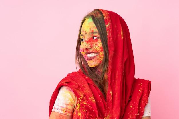 Młoda indiańska kobieta z kolorowymi holi proszkami na jej twarzy na menchii ścianie szczęśliwej i uśmiechniętej
