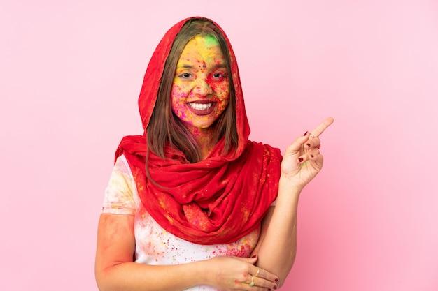 Młoda indiańska kobieta z kolorowymi holi proszkami na jej twarzy odizolowywającej na menchiach izoluje szczęśliwy i wskazuje up