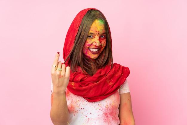 Młoda indiańska kobieta z kolorowymi holi proszkami na jej twarzy odizolowywającej na menchii ścianie robi nadchodzącemu gestowi