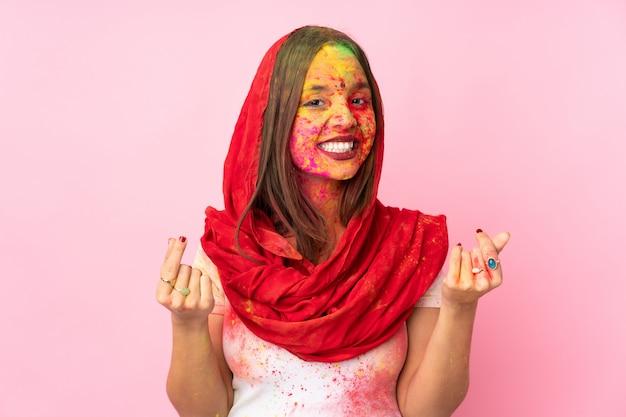 Młoda indiańska kobieta z kolorowymi holi proszkami na jej twarzy odizolowywającej na menchii ścianie robi pieniądze gestowi