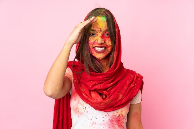 Młoda indiańska kobieta z kolorowymi holi proszkami na jej twarzy odizolowywającej na menchii ścianie salutuje z ręką z szczęśliwym wyrażeniem
