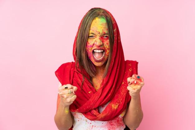 Młoda indiańska kobieta z kolorowymi holi proszkami na jej twarzy odizolowywającej na menchii ścianie świętuje zwycięstwo w zwycięzca pozyci