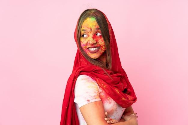 Młoda indiańska kobieta z kolorowymi holi proszkami na jej twarzy odizolowywającej na menchii ścianie z rękami krzyżować i szczęśliwy