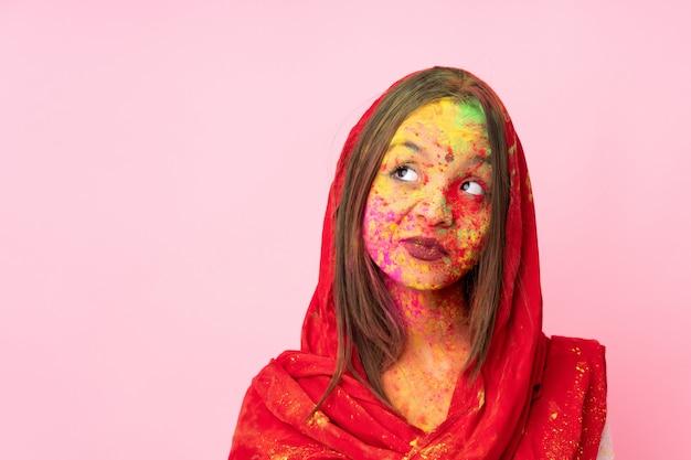 Młoda indiańska kobieta z kolorowymi holi pudruje na jej twarzy na menchii ścianie ma wątpliwości podczas gdy patrzejący stronę