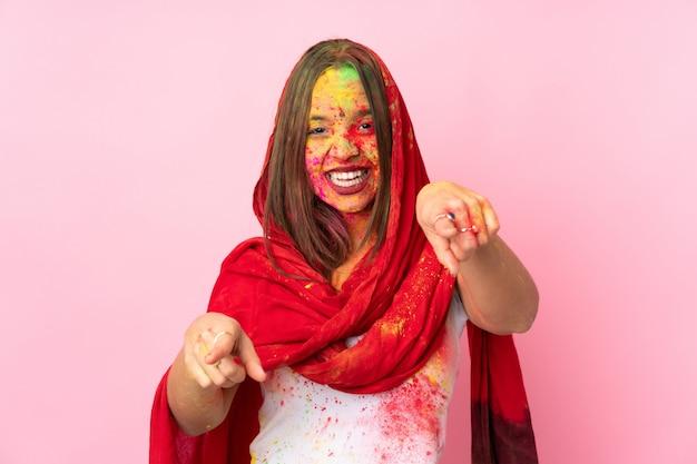 Młoda indiańska kobieta z kolorowymi holi pudruje na jej twarzy na menchii ścianie wskazuje przód z szczęśliwym wyrażeniem