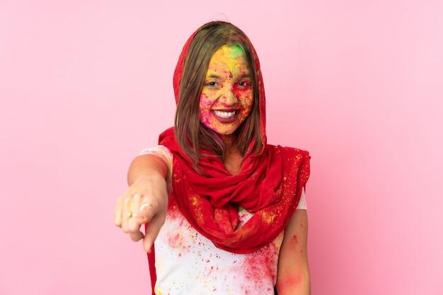 Młoda indiańska kobieta z kolorowymi holi pudruje na jej twarzy odizolowywającej na menchii ścianie wskazuje przód z szczęśliwym wyrażeniem
