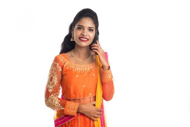 Młoda indiańska tradycyjna dziewczyna używa telefon komórkowego lub smartphone odizolowywających na białej ścianie