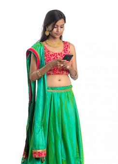Młoda indiańska tradycyjna dziewczyna używa telefon komórkowego lub smartphone odizolowywających na bielu