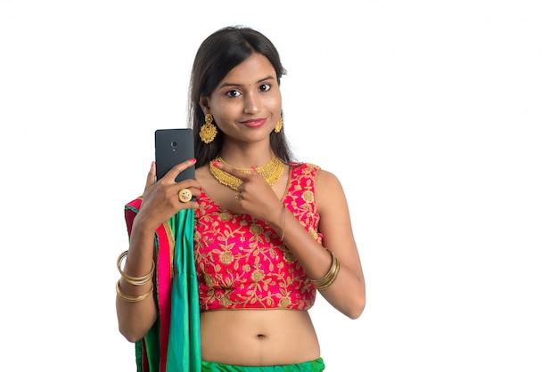Młoda indiańska tradycyjna kobieta używa telefon komórkowego lub smartphone odizolowywających na białej ścianie