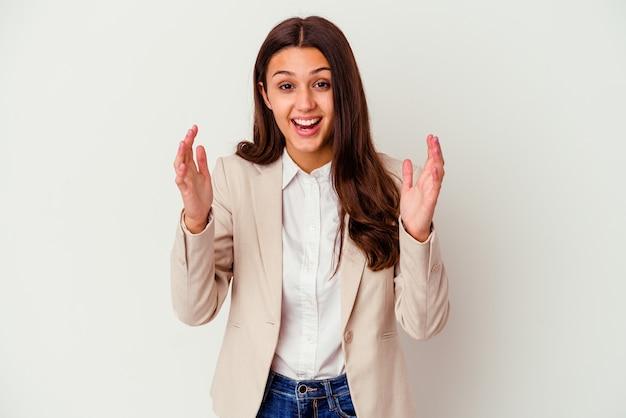 Młoda indyjska biznesowa kobieta odizolowywająca na białym tle otrzymująca miłą niespodziankę, podekscytowana i podnosząca ręce.