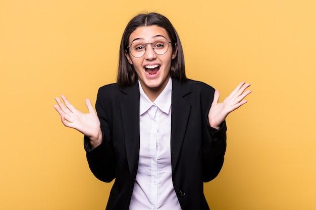 Młoda indyjska kobieta biznesu na białym tle na żółtej ścianie świętuje zwycięstwo lub sukces, jest zaskoczony i zszokowany.