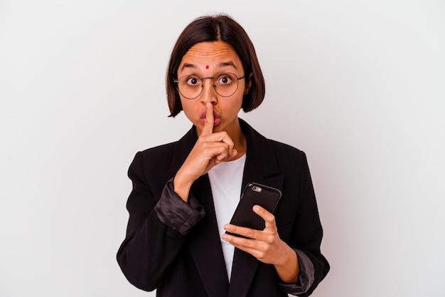 Młoda indyjska kobieta biznesu trzyma telefon na białym tle, zachowując tajemnicę lub prosząc o ciszę.