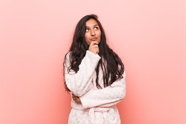 Młoda indyjska kobieta jest ubranym piżamę patrzeje z ukosa z wątpliwym i sceptycznym wyrażeniem.
