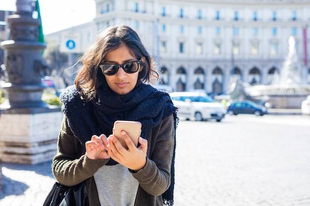 Młoda indyjska kobieta korzystająca z telefonu komórkowego na ulicy