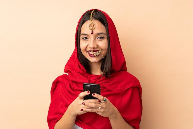 Młoda indyjska kobieta na beżowej ścianie wysyła wiadomość z wiszącą ozdobą