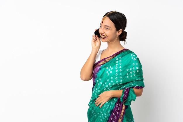 Młoda indyjska kobieta na białej ścianie prowadzenia rozmowy z telefonem komórkowym z kimś