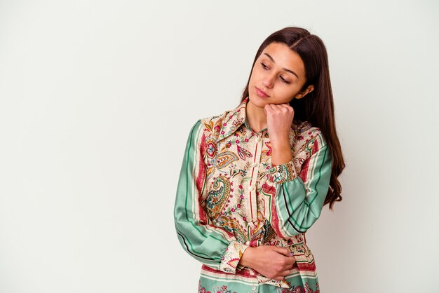 Młoda indyjska kobieta na białym tle, która czuje się smutna i zamyślona, patrząc na miejsce.