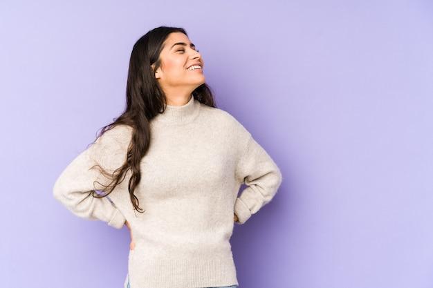 Młoda indyjska kobieta na białym tle na fioletowy zrelaksowany i szczęśliwy, śmiejąc się, wyciągnięta szyja pokazująca zęby.
