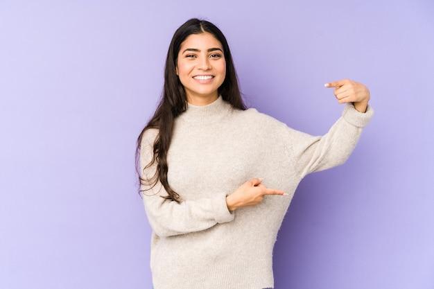 Młoda indyjska kobieta na białym tle na fioletowym tle trzyma coś małego z palcami wskazującymi, uśmiechnięta i pewna siebie.