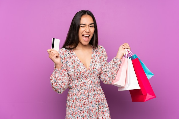 Młoda indyjska kobieta na białym tle na fioletowym tle, trzymając torby na zakupy i kartę kredytową
