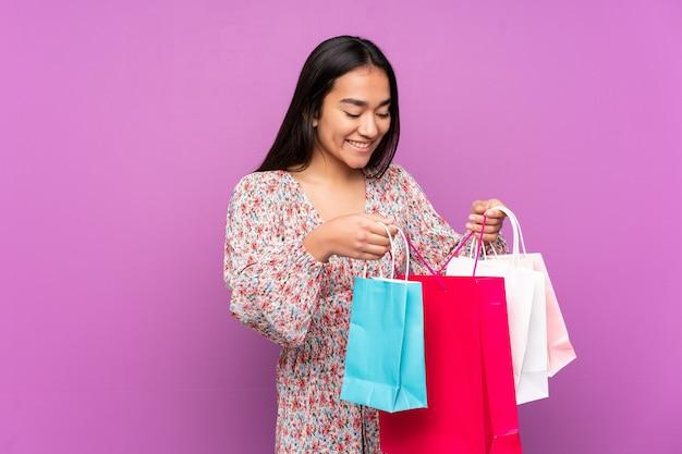 Młoda indyjska kobieta na białym tle na fioletowym tle, trzymając torby na zakupy i patrząc wewnątrz niego
