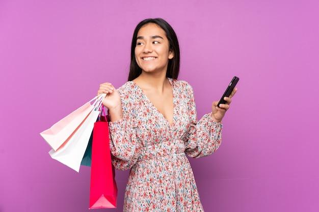 Młoda indyjska kobieta na białym tle na fioletowym tle, trzymając torby na zakupy i telefon komórkowy