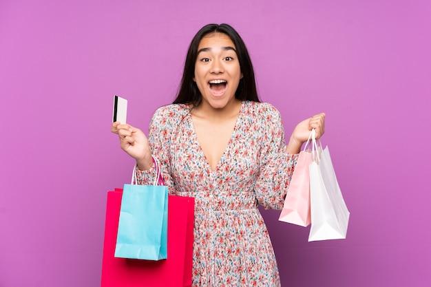 Młoda indyjska kobieta na białym tle na fioletowym tle trzymając torby na zakupy i zaskoczony