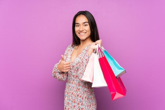 Młoda indyjska kobieta na białym tle na fioletowym tle trzymając torby na zakupy iz kciukiem do góry