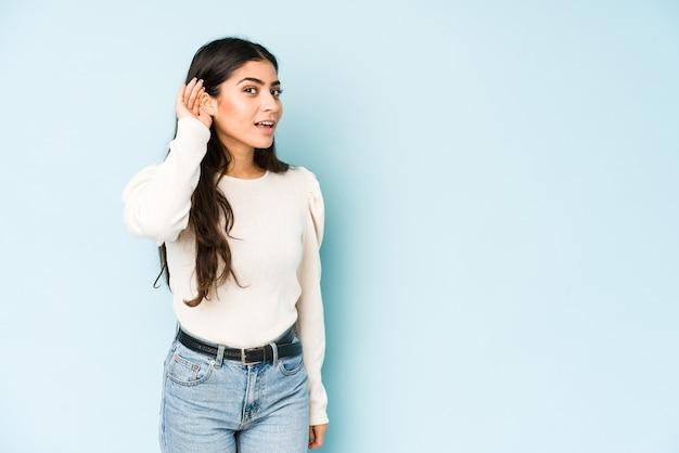 Młoda indyjska kobieta na białym tle na niebieskiej ścianie próbuje słuchać plotek.