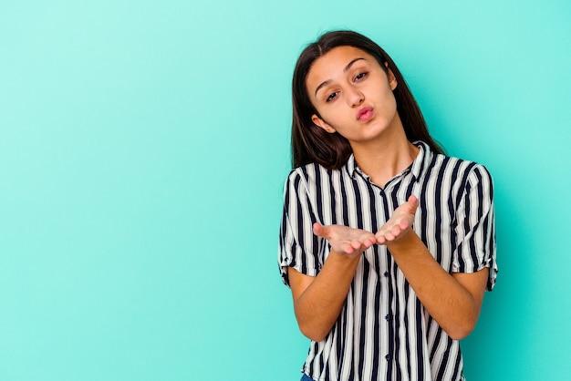 Młoda indyjska kobieta na białym tle na niebieskim tle składane usta i trzymając dłonie, aby wysłać pocałunek powietrza.