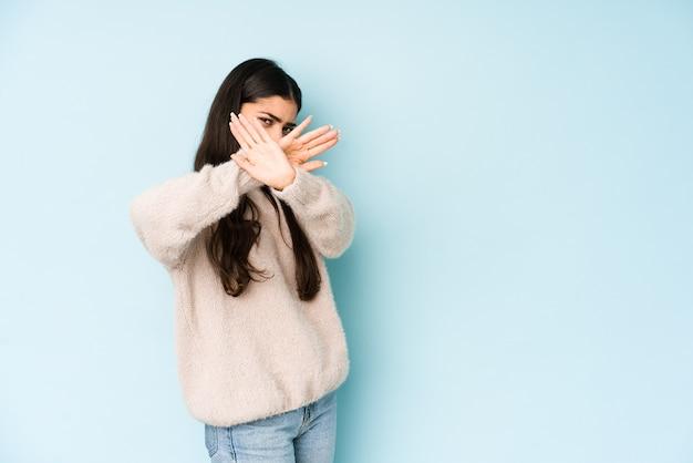 Młoda indyjska kobieta na białym tle na niebiesko, trzymając skrzyżowane ręce, pojęcie odmowy.
