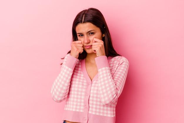 Młoda indyjska kobieta na białym tle na różowym tle skomle i płacze niepocieszony.