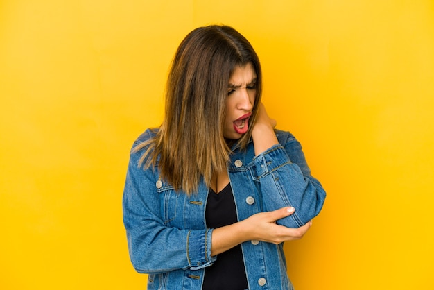 Młoda indyjska kobieta na białym tle na żółtym tle masuje łokieć, cierpi po złym ruchu.
