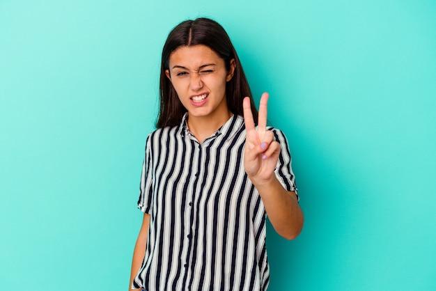 Młoda indyjska kobieta na niebiesko pokazuje numer dwa palcami.