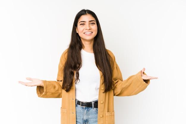 Młoda indyjska kobieta na purpury ścianie pokazuje mile widziany wyrażenie.