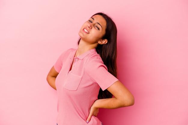 Młoda indyjska kobieta na różowym tle cierpi na ból pleców.