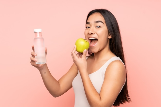 Młoda indyjska kobieta na różowym tle z jabłkiem i butelką wody