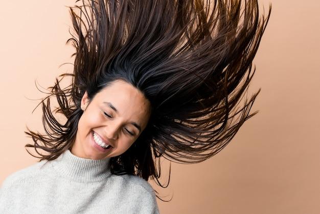 Młoda indyjska kobieta poruszająca włosami na białym tle na beżowym tle