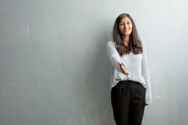 Młoda indyjska kobieta przeciw grunge ścianie dosięga out witać someone lub gestykulować pomagać, szczęśliwy i z podnieceniem
