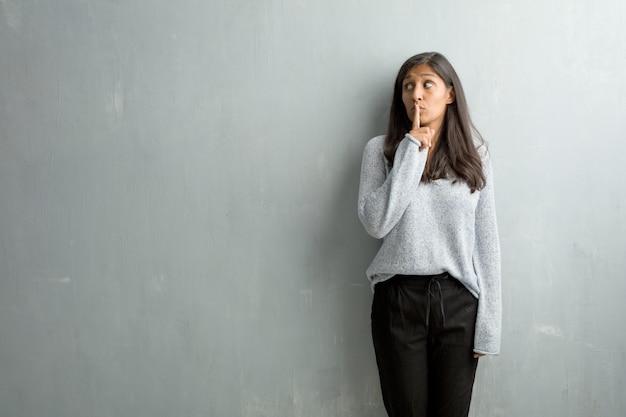 Młoda indyjska kobieta przeciw grunge ścianie utrzymuje sekret lub pytać dla ciszy